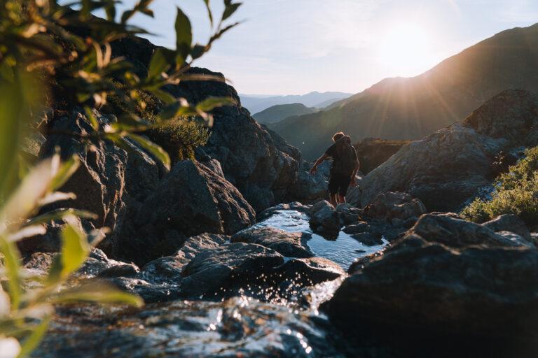 Naturbilde fra Hemsedal med en fotturist som går i en steinrøys med en bekk, sommerstid med sol og blå himmel.
