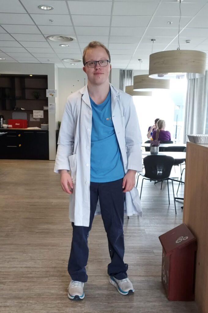 Bilde av ung mann i hvit frakk og blå t-skjorte, i helfigur. Tatt i kantinen.
