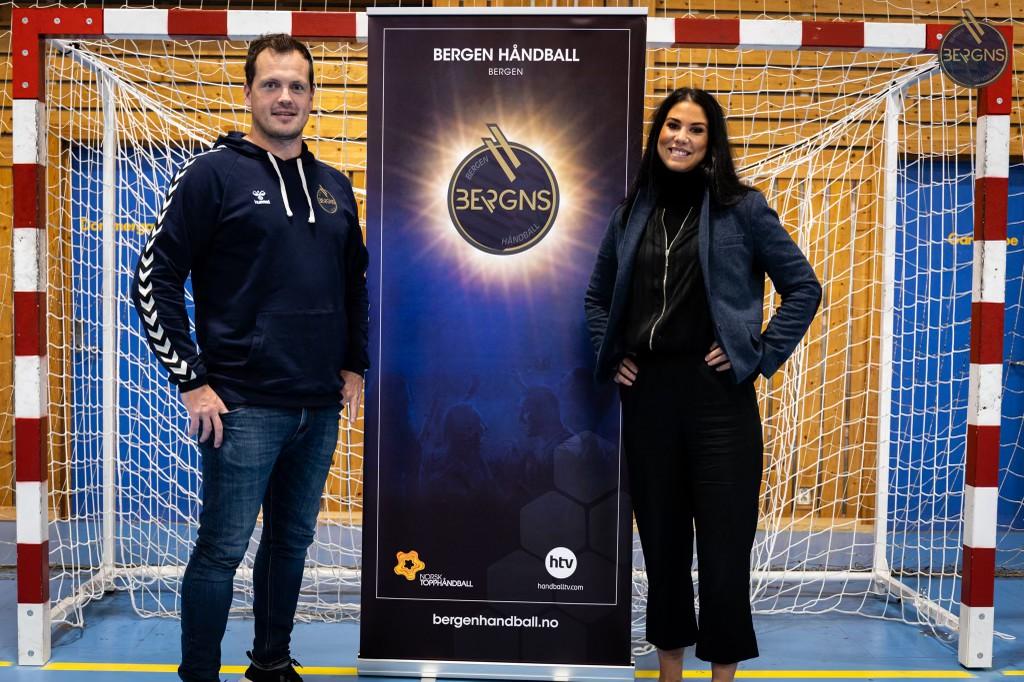 Hvit mann med mørk brunt hår står foran et håndballmål, med en dame med mørskt hår, kledd i svart til høyre. Roll-up med Bergen Håndballs logo i midten.
