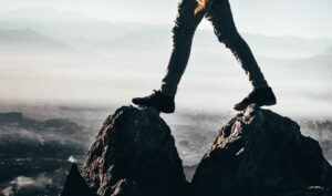 Illustrasjonsbilde av en mann som går fra en stein til en annen på et fjell. Kun føtter i fokus, med uklar bakgrunn.