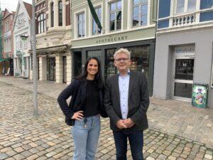 Bilde av to mennesker ute på gaten i Bergen: dame med svart hår og svart genser og jeans til venstre, og hivt, litt eldre mann med grått hår og briller i dress til høyre.
